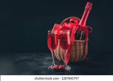 Valentine's day greeting card with champagne and gift hamper on black. Space for your greetings.