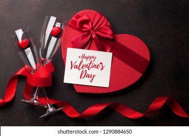 Valentine's day greeting card with champagne glasses and gift box on stone background. Top view with space for your greetings. Flat lay