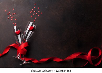 Valentine's day greeting card with champagne glasses and heart candy on stone background. Top view with space for your greetings. Flat lay