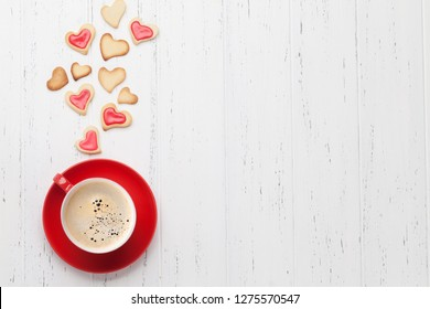 Valentine's day greeting card with coffee cup and heart shaped cookies on wooden background. Top view with space for your greetings. Flat lay