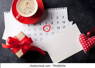 Valentines day greeting card, coffee cup and gift box over february calendar on stone table. Top view with copy space