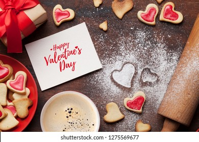 Valentine's day greeting card with cooking heart shaped cookies on wooden background. Top view with space for your greetings. Flat lay