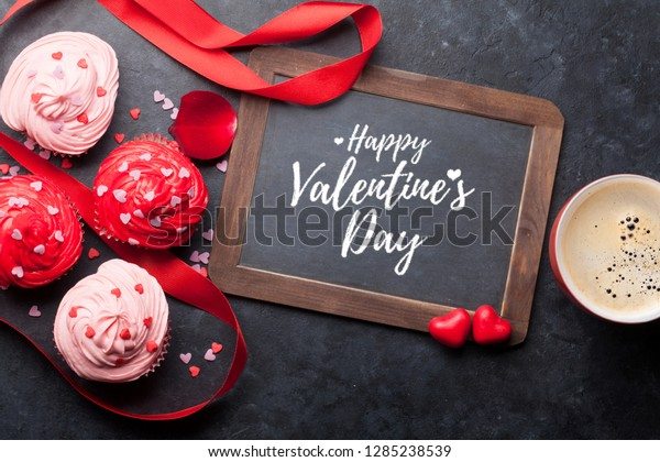 Valentine's day greeting card with delicious sweet cupcakes and coffee cup on stone background. Top view