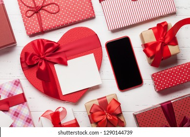 Valentine's day greeting card with gift boxes and smartphone on wooden background. Top view with space for your greetings or smart phone app. Flat lay