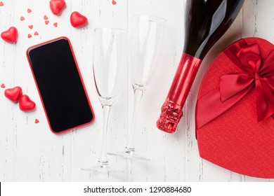 Valentine's day greeting card with gift box, champagne and smartphone on wooden background. Top view with space for your greetings or smart phone app. Flat lay