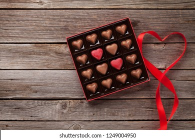 Valentines day greeting card with heart chocolate in box on wooden table. Top view with space for your greetings