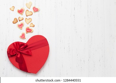Valentine's day greeting card with heart shaped cookies and gift box on wooden background. Top view with space for your greetings. Flat lay