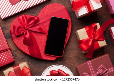 Valentine's day greeting card with heart gift boxes and smartphone on wooden background. Top view with space for your greetings or smart phone app. Flat lay
