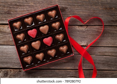 Valentines day greeting card with heart chocolate box on wooden table. Top view