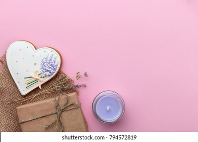 Valentines Day greeting card with heart shaped gingerbread, thyme flowers, gift box and candle on rose paper background