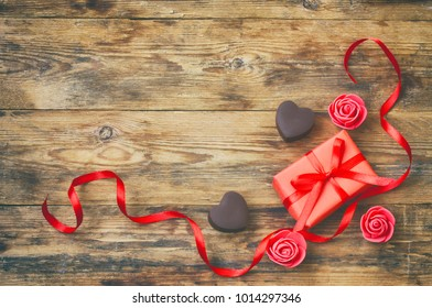 valentines day greeting card, milk chocolate heart shape, gift box, red satin ribbon, roses flowers on wooden table