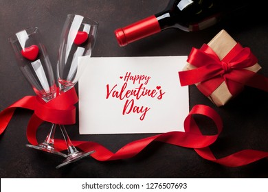 Valentine's day greeting card with red wine bottle and love gift box on stone background. Top view with space for your greetings. Flat lay
