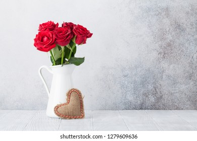 Valentine's day greeting card with red rose flowers bouquet and knitted heart in front of stone wall. With space for your greetings