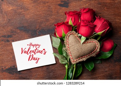 Valentine's day greeting card with red rose flowers bouquet and knitted heart on wooden background. Top view with space for your greetings