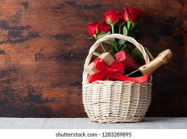 Valentine's day greeting card with red rose flowers bouquet and champagne in basket on wooden background. With space for your greetings