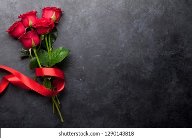 Valentine's day greeting card with red rose flowers bouquet on stone background. Top view with space for your greetings
