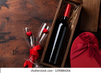 Valentine's day greeting card with red wine bottle and love gift box on wooden background. Top view with space for your greetings. Flat lay