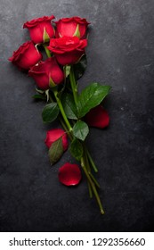 Valentine's day greeting card with red rose flowers bouquet on stone background. Top view