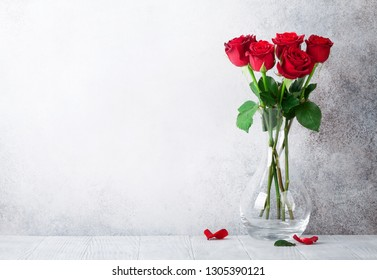 Valentine's day greeting card with red rose flowers bouquet in front of stone wall. With space for your greetings