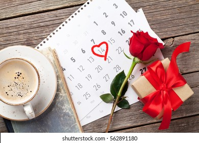 Valentines day greeting card. Red rose, coffee cup and gift box over february calendar on wooden table. Top view