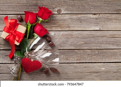Valentines day greeting card. Red roses, heart, wine glasses, chocolate and gift box on wooden table. Top view with copy space