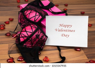 Valentines day greeting card and seductive black lingerie bra gift and red hearts