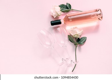 Valentines day greeting card.  White roses, wine and glasses for wine on a soft light pink on wood table. Flat lay, top view, copy space