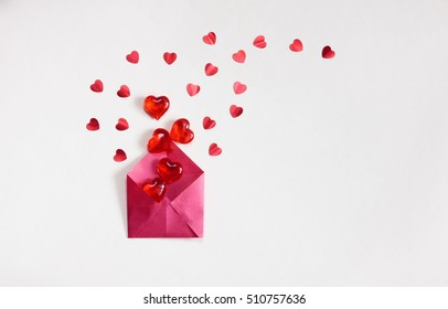 valentine's day, grey background, red envelope with lots of transparent sweet hearts and confetti