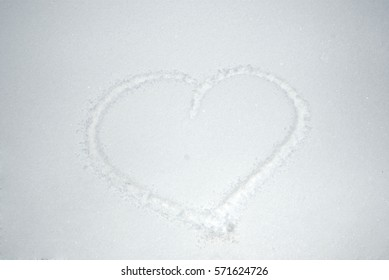 Valentine's day. Hand drawing heart in the snow. Snow heart shape. Heart on the snow closeup.