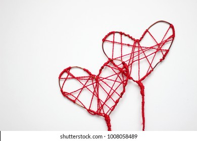 Valentine's Day Handmade Red Thread Hearts over white background. Valentine's Day Holiday Background with hearts. Beautiful Hearts. Holiday of Love. Wedding celebrating. Art design.