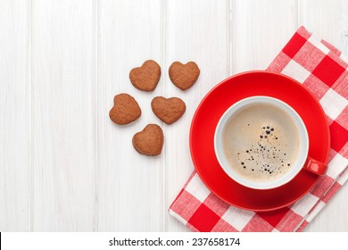 Valentines day heart shaped cookies and red coffee cup. View from above with copy space