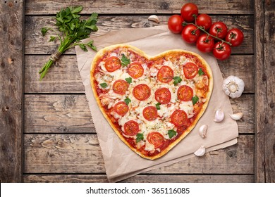Valentines day heart shaped pizza margherita vegetarian love concept with mozzarella. tomatoes, parsley and garlic on vintage wooden table background.