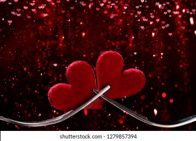 Valentine's Day, hearts and forks against bokeh background