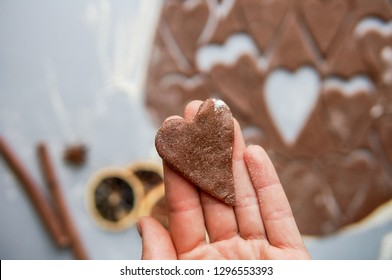 Valentine's Day heart-shaped cookies background. Woman hand holding a biscuit heart