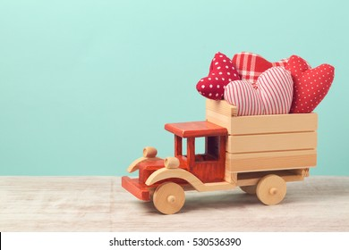 Valentine's day holiday concept with toy truck and heart shapes over mint background