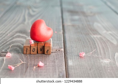 """Valentine's day interior decoration in the form of old wooden letters with the word """"Love"""" and red heart on the table in a living room"""
