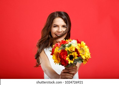Valentines Day. Love. Beautiful smiling girl holding a bouquet of flowers. Laughing woman giving a present. Celebrate a happy holiday. Give flowers as a gift. Joyful festive mood. Red background.