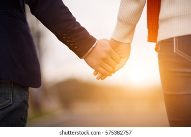 Valentines day and love concept background image.A heterosexual couple holding hands and walking together outdoors at sunset.