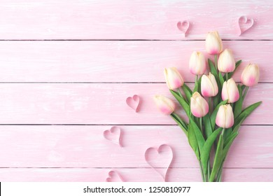 Valentines day and love concept. Pink paper hearts with  tulips on pink pastel wooden background.