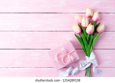 Valentines day and love concept. Pink paper hearts with gift box and tulips with ribbon on pink pastel wooden background.