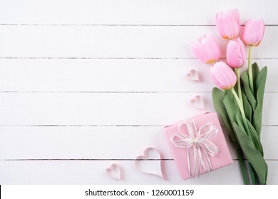Valentines day and love concept. Pink paper hearts with gift box and tulips with ribbon on white wooden background.
