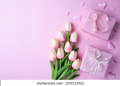 Valentines day and love concept. Pink tulips, gift box with heart on pink background.