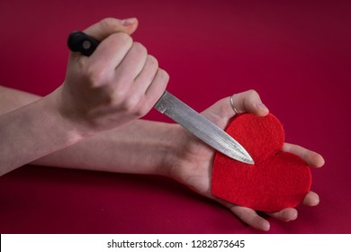 Valentines Day. Love heart. Breakheart. Female hand and pierces it heart knife.