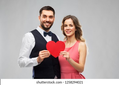 valentines day, love and people concept - happy couple in party clothes with red heart over grey background