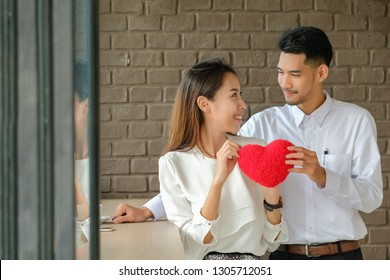 Valentine's Day man gave the red heart to girl to show love.