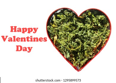 Valentines Day Marijuana. Dried Marijuana Leaves and Flowers in a Heart Shape. Ganga in a Red Heart Shape Cookie Cutter. Room for Text. Isolated on white. Text reads Happy Valentines Day.