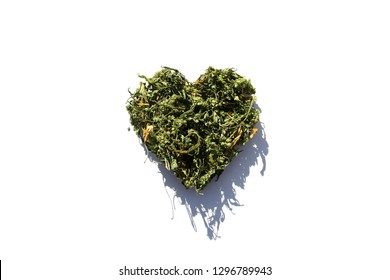 Valentines Day Marijuana. Dried Marijuana Leaves and Flowers in a Heart Shape. Valentines day Images. I LOVE Marijuana. I LOVE Cannabis. Green Pot Leaves on white.