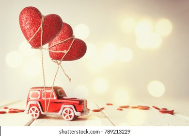 Valentines Day message with miniature red car. Heart shape balloon and car toy on wooden table. Valentine's day concept.