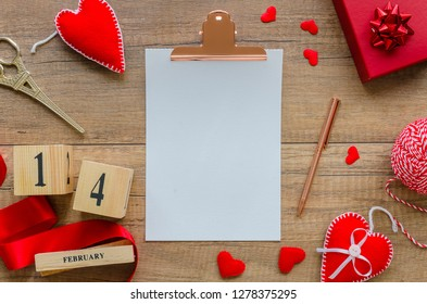 Valentines day mockup. Flat lay composition from red hearts, ribbon, perpetual calendar date 14 february, gift box, pen on wooden background with blank paper sheet a5. Saint Valentine day decoration