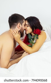 Valentines day morning bed just married couple celebration heart gift surprise rose. She stroking his face